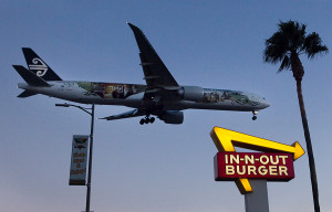 An Air New Zealand Boeing 777 aircraft lands in front of an In-N-Out restaurant near Los Angeles International Airport (LAX). Photo by John Schreiber.