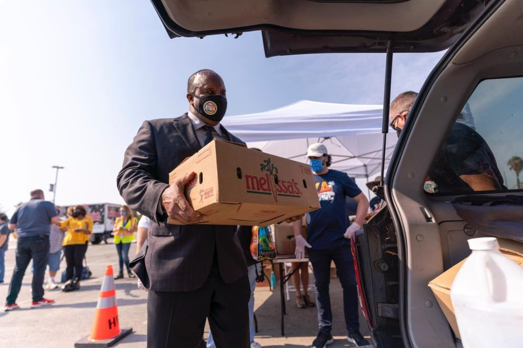 Mayor Butts hands out food at the One For All backpack giveaway by Mari Morales at SoFi Stadium August 24, 2020. (photo: city of Inglewood)